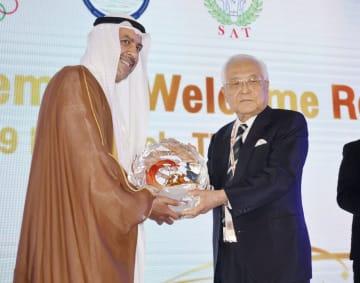 アジア・オリンピック評議会の総会でアハマド会長(左)から特別表彰を受ける広島市の平岡敬元市長=2日、バンコク(共同)