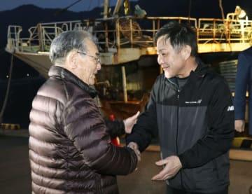 境港に到着し、迎えられるカニ漁船「第68西野丸」船長の利見秀治さん(右)=3日午前、鳥取県境港市