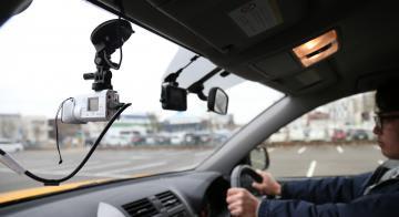 道路パトロール車のフロントガラスに設置された路面撮影用のビデオカメラ(左手前)で破損を検出する=つくば市内