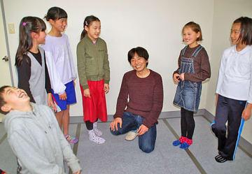 岡田さん(中央右)のアドバイスを笑顔で聞く6人のキッズ劇団員=倉吉市内