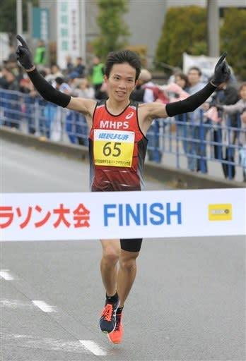 ハーフマラソンで1位となり、両手を掲げてフィニッシュする井上大仁選手(MHPS)=玉名市役所前