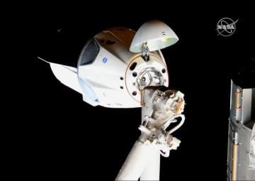 国際宇宙ステーションに到着し、ドッキングのため接近する有人型ドラゴン宇宙船(中央のカプセル)。手前はロボットアームの一部(NASAテレビ)