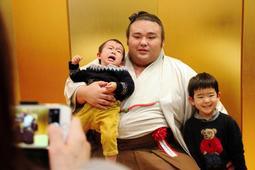 赤ちゃんを抱っこして撮影に挑む大相撲の貴景勝関=3日午後、阪急西宮ガーデンズ、西宮市高松町