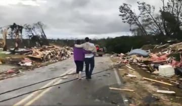 3日、米アラバマ州リー郡で、竜巻被害とみられるがれきの中を歩く人々(WKRG―TV提供、AP=共同)
