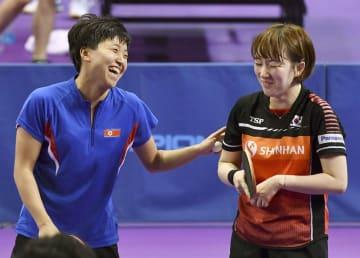 2018年7月、合同練習で笑顔を見せる北朝鮮選手(左)と韓国選手=韓国・大田(共同)