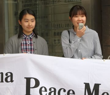 出発式であいさつする中村さん(右)と山口さん=長崎市大黒町