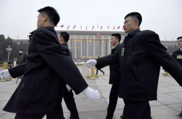 中国全人代が開かれる人民大会堂前で警備する治安当局者=5日、北京(共同)