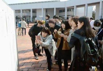 県立大一般入試前期日程の合格者が発表され、自分の受験番号を確認する受験生ら=5日、熊本市東区