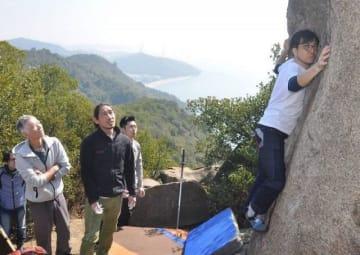 王子が岳でボルダリングに挑戦する佐久間さん(右)
