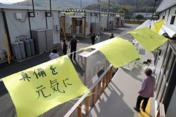 仮設住宅の軒先で風になびく黄色い小旗。1枚1枚のメッセージに復興への思いが込められている=倉敷市真備町箭田、真備総