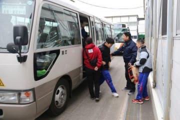 倉敷支援学校内の仮校舎に到着し、スクールバスから降りる倉敷まきび支援学校の生徒=2月下旬