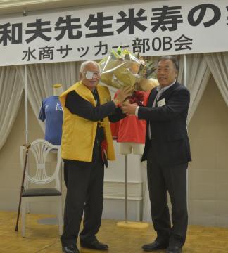 米寿を祝う集いで花束を受け取る助川和夫さん(左)=水戸市白梅