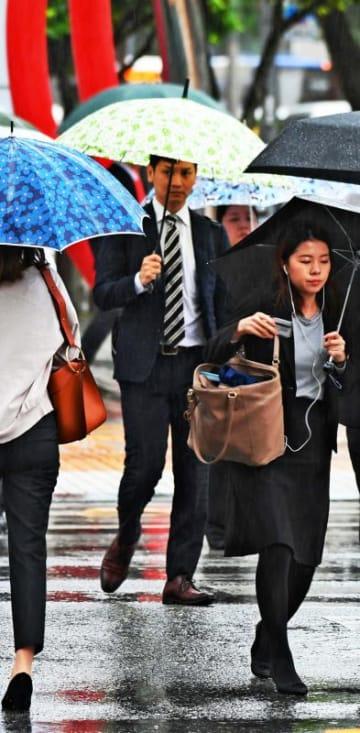 時折激しい雨が降る中、通勤する人たち=6日午前8時39分、那覇市久茂地