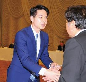 自民党主催の会合で出席者と名刺を交わす鈴木氏
