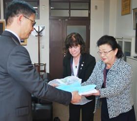 奥本校長に雑巾を手渡す熊谷部長(右)と三河副部長(中央)