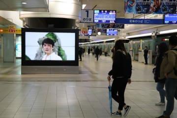 乗降客に県内離島をPRする福山さん出演の動画=福岡市中央区、西鉄福岡(天神)駅
