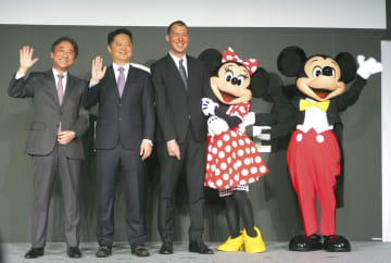 記者会見を開き記念撮影するNTTドコモの吉沢和弘社長(左端)とウォルト・ディズニー・ジャパンのトニー・エリソン氏(左から3人目)ら=7日午後、東京都目黒区