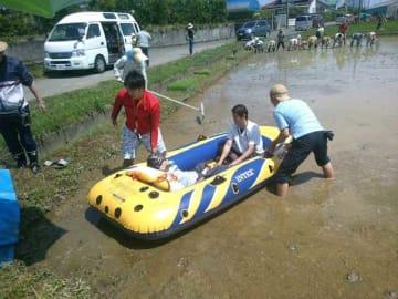 田植えをする住民や患者ら。体が不自由な人はボランティアらが手助けし、ボートに乗って作業をする(日高さん提供)