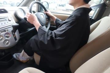 白衣と布袍を着て車の運転席に座る僧侶(取り締まりを受けた僧侶ではありません)=1月10日、福井市