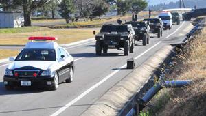 パトカーの先導で訓練場所に移動する軽装甲機動車