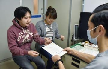 禁煙外来の医師から治療の「終了証書」を受け取る加藤誠司さん(左端)、秀実さん(中央)夫妻