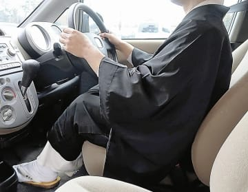 福井県警が青切符を切ったケースと同様に、白衣と布袍を着て車の運転席に座る僧侶=福井県福井市