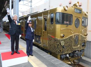 水戸岡さん(左)と西島駅長の合図で出発する「或る列車」=佐世保市、JR佐世保駅