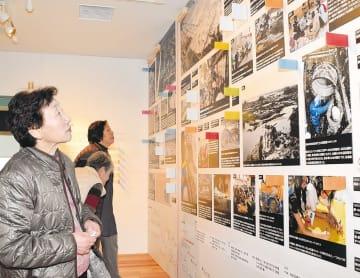 常設展の写真パネルで沿岸部の被害状況を確かめる来館者