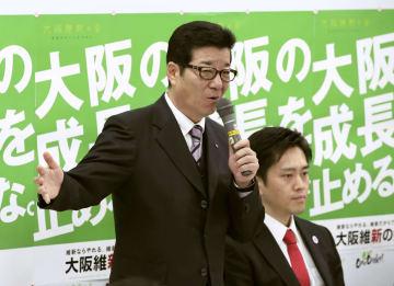 大阪維新の会の会合であいさつする松井一郎大阪府知事。自身が市長選に、吉村洋文大阪市長(右)が知事選にそれぞれ入れ替わって立候補すると表明した=8日午後、大阪市