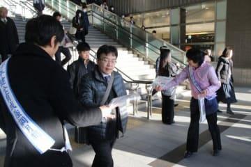 駅利用者にちらしを配る県警や県教委の関係者ら=JR岡山駅