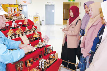 人形の名前や役割などの説明を聞くインドネシア人の技能実習生