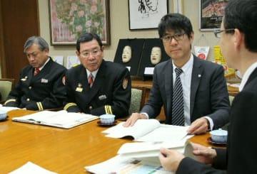 消防団ビジョンを佐藤樹一郎市長(右端)に説明する鶴成悦久委員長(右から2人目)と嵯峨健司団長(同3人目)