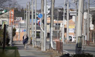 日中も人通りの少ない福島県浪江町の中心部。避難解除後に自宅に戻ったという高齢女性は「周囲の人たちはなかなか帰ってこない」と話した=2月