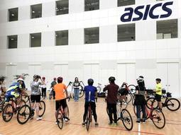 終業後にアシックス本社内の体育館で開かれた自転車イベント(同社提供)
