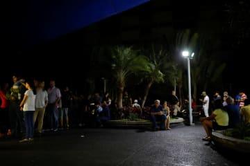 停電が発生したベネズエラの首都カラカスで、買い物をしようと薬局の前に並ぶ市民=8日(ロイター=共同)