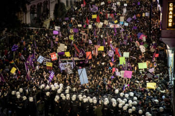 8日、トルコ・イスタンブールのデモに参加した女性たちを強制排除しようとする警官(ゲッティ=共同)