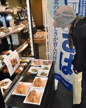 限定販売のサバ商品を品定めする市民=8日、さくら野八戸店