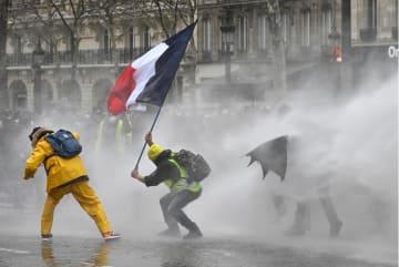 9日、パリ中心部のシャンゼリゼ大通りで、警官隊からの放水を受けるデモ隊(ゲッティ=共同)