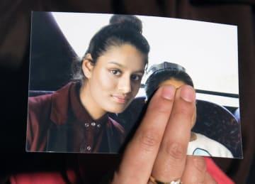 シャミマ・ベグムさん(左)の写真を持つ親族=2015年2月、ロンドン(ロイター=共同)