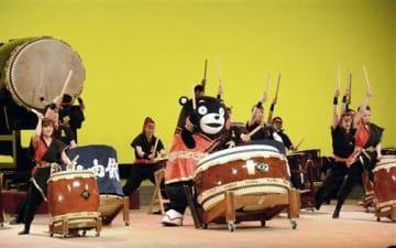 誕生祭で必由館高和太鼓部と一緒にステージに立ち、ばちさばきを披露するくまモン=9日、熊本市中央区
