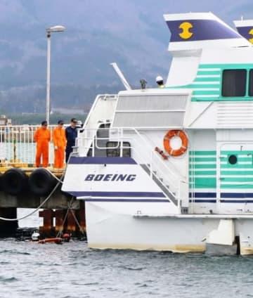 船尾付近を潜水調査する海保職員と、岸壁から船体を調べる運輸安全委員会の調査官ら=10日午後2時30分前、佐渡市の両津港