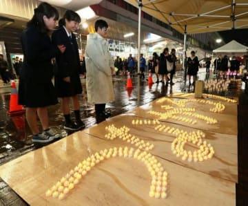 東日本大震災被災地の復興を祈り、並べられたキャンドル=10日午後6時51分、JR岡山駅東口広場