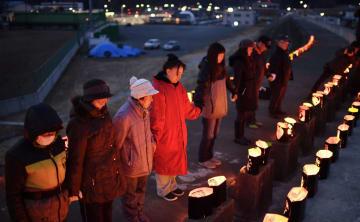 灯籠のあかりの中で、東日本大震災の犠牲者を悼み黙とうする人たち=10日午後5時54分、岩手県宮古市