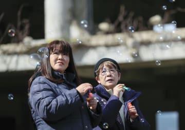 宮城県石巻市の旧大川小校舎で、鈴木実穂さん(左)とシャボン玉を飛ばす美谷島邦子さん=10日午後0時57分