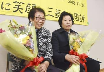 市民団体が開いた集会で、勝訴を祝う花束を受け取り喜ぶ梁錦徳さん(左)ら=10日、名古屋市