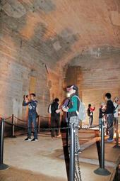 巨大防空壕の内部を見学するツアーの参加者=2018年10月、加西市鶉野町