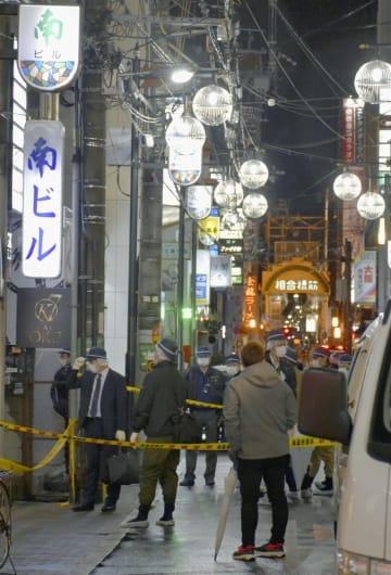 発砲事件現場付近を調べる大阪府警の捜査員=11日午前3時1分、大阪市中央区