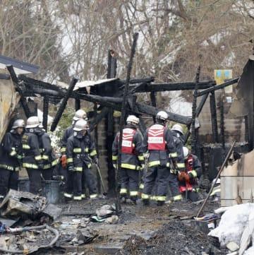 火災が起きた現場で作業する消防隊員=11日午前9時20分、青森県弘前市
