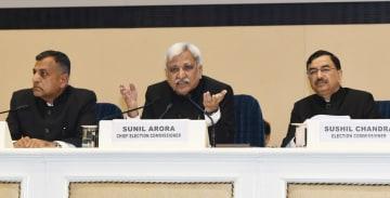 10日、ニューデリーで総選挙日程を発表する選管委のアロラ委員長(中央)=インド政府提供