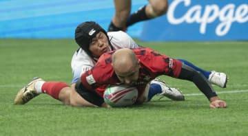 ラグビー7人制男子ワールドシリーズ ウェールズ戦で競り合う石田吉平(上)=10日、バンクーバー(ゲッティ=共同)